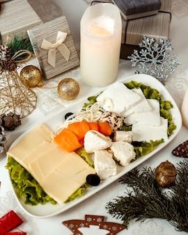 Prato de queijo com alperce fatiado e azeitonas