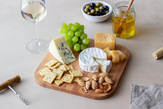 Prato de queijo com bolacha, amêndoas e uvas. aperitivo de vinho. petisco de vinho.
