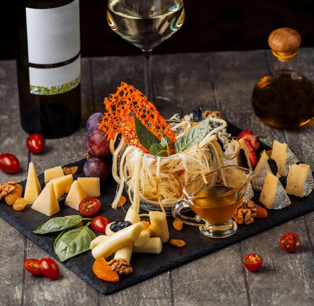 Prato de queijo com copo de vidro de queijo defumado no meio