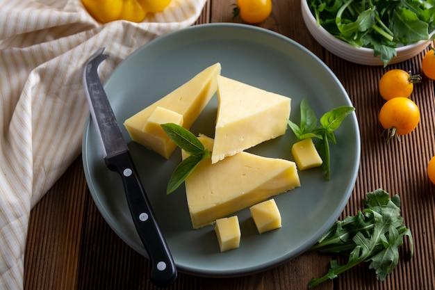Prato de queijo com fatias de queijo delicous e uma faca de queijo, mesa de madeira.
