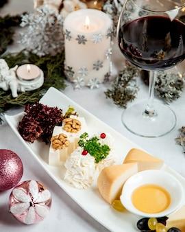 Prato de queijo com nozes e taça de vinho