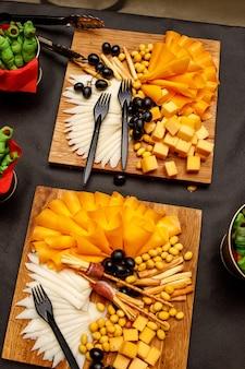 Prato de queijo com outros petiscos em uma mesa de banquete.