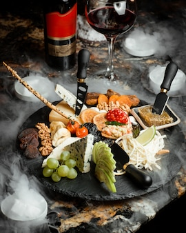 Prato de queijo com queijo parmesão azul e branco frutas e nozes