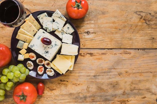 Prato de queijo com tomate e uvas na mesa de madeira