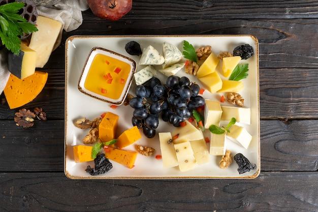 Prato de queijo com uvas, mel, ameixas e nozes.
