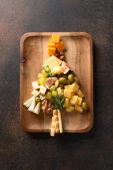 Prato de queijo como árvore de natal com diferentes queijos e aperitivos