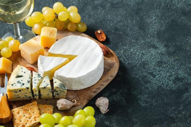 Prato de queijo de degustação em um prato de pedra escura.