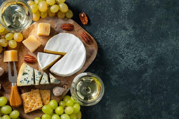 Prato de queijo de degustação em uma placa de madeira.