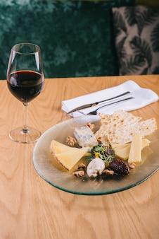 Prato de queijo na mesa com uvas e nozes petiscos para vinho