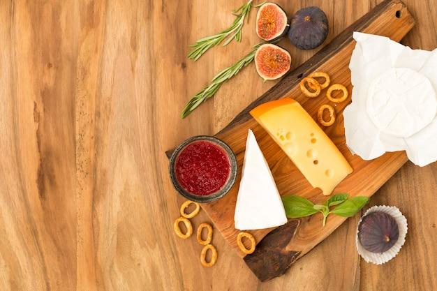 Prato de queijo servido com geléia, figos, biscoitos e ervas em um fundo de madeira.