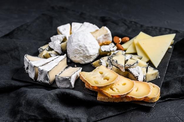 Prato de queijo servido com nozes e figos. aperitivo francês. fundo preto. vista do topo