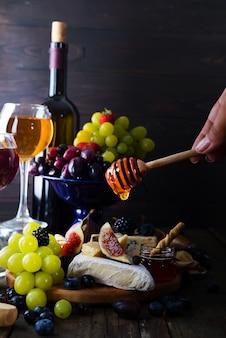 Prato de queijo servido com vinho, geléia e na mão um pau com mel