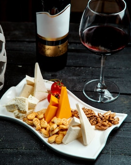 Prato de queijos com copo de vinho tinto