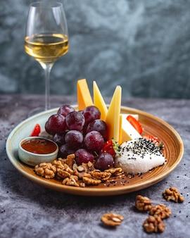 Prato de queijos com nozes, queijo cheddar de uvas, queijo de cabra, mussarela, queijo azul e morangos servido com vinho branco