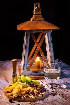Prato de queijos com uma variedade de petiscos na mesa com duas taças de vinho à luz de velas