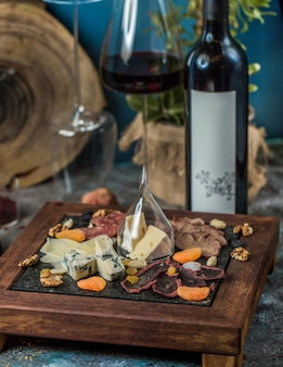 Prato de queijos e um copo com uma garrafa de vinho tinto