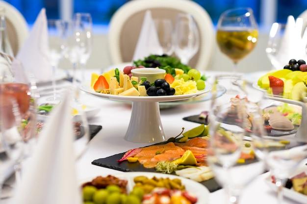 Prato de queijos na mesa com frutas e outros pratos com carne e picadinho em mesa de banquete