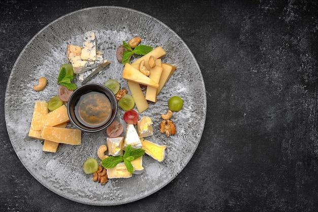 Prato de queijos, queijos variados com hortelã, frutas cristalizadas, mel e biscoitos, em um prato
