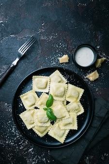 Prato de ravióli com cogumelos e queijo decorado com manjericão na pedra escura