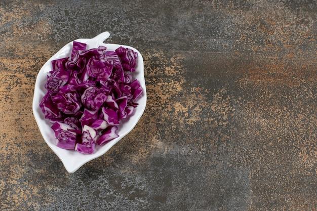Prato de repolho roxo em forma de folha, na superfície de mármore
