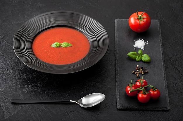 Prato de restaurante preto de sopa cremosa de tomate e colher em preto com tábua de pedra e tomates crus, pimenta e sal.