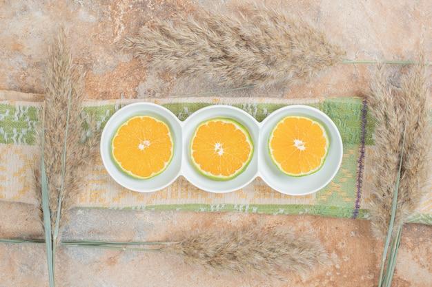 Prato de rodelas de limão na superfície de mármore com toalha de mesa e planta.