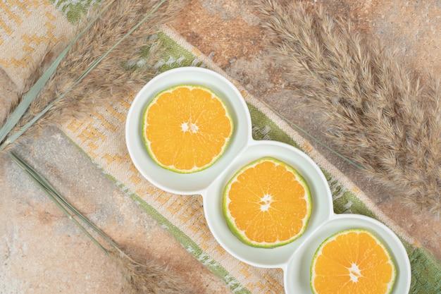 Prato de rodelas de limão na superfície de mármore com toalha de mesa.