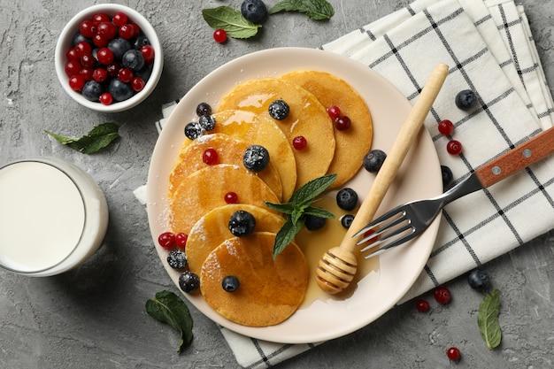 Prato de saborosas panquecas com berry na mesa cinza. composição do café da manhã doce