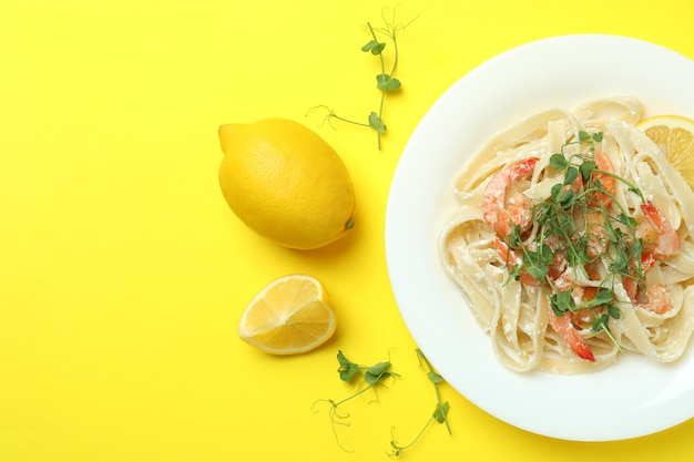 Prato de saboroso macarrão de camarão em fundo amarelo