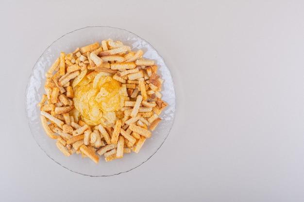 Prato de saborosos biscoitos crocantes e batatas fritas no fundo branco. foto de alta qualidade