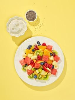 Prato de salada de frutas em fundo amarelo, vista superior