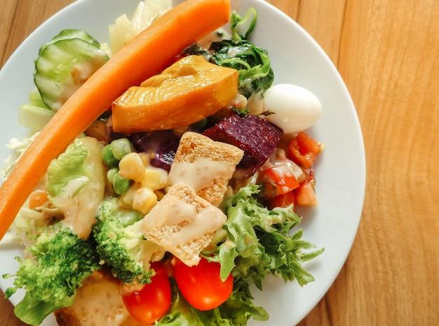 Prato de salada de vegetais orgânicos frescos de alface, cenoura, pepino, cebola, espinafre, tomate, peito e ovo.