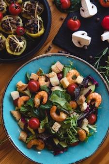 Prato de salada fresca com camarão, tomate e verduras mistas (rúcula, mesclun, mache) em fundo de madeira close-up. comida saudável. comer limpo.