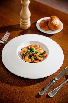 Prato de salada fresca com camarão, tomate e verduras na superfície de madeira close-up