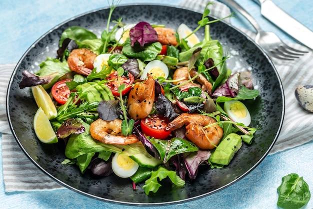 Prato de salada fresca com tomate cereja, pepino, abacate, ovos e camarões defumados, verdes mistos. comida saudável. comer limpo. fundo de receita de comida. fechar-se.