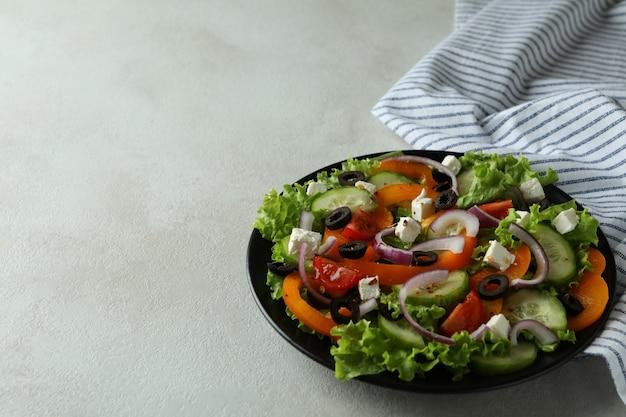Prato de salada grega e toalha de cozinha em superfície texturizada branca