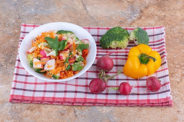 Prato de salada mista ao lado de vários vegetais em uma toalha na superfície de mármore