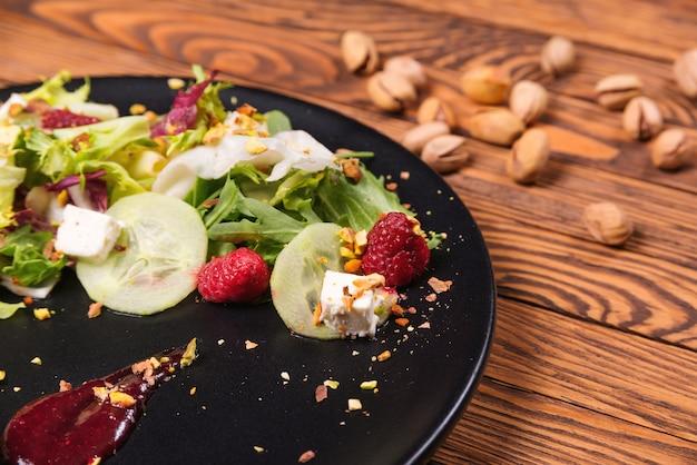 Prato de salada saudável com rúcula, queijo branco e framboesas. conceito de comida de dieta saudável.