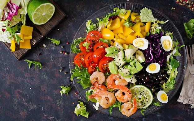 Prato de salada saudável. receita de frutos do mar frescos. camarão grelhado e salada de legumes frescos - abacate, tomate, feijão preto, couve roxa e páprica. camarões grelhados.