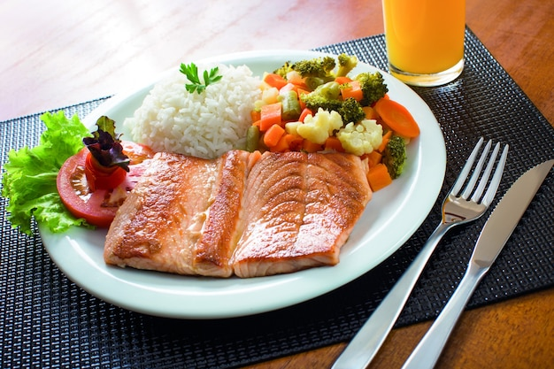 Prato de salmão com legumes, arroz, salada e suco de laranja