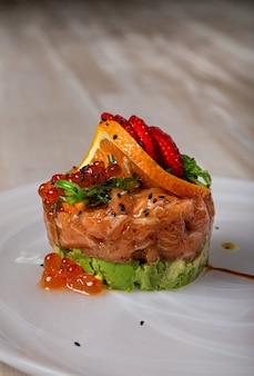 Prato de salmão decorado com uma rodela de laranja, morangos e sementes de chia