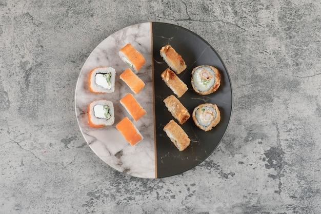 Prato de salmão e rolinhos de sushi quentes colocados na mesa de mármore