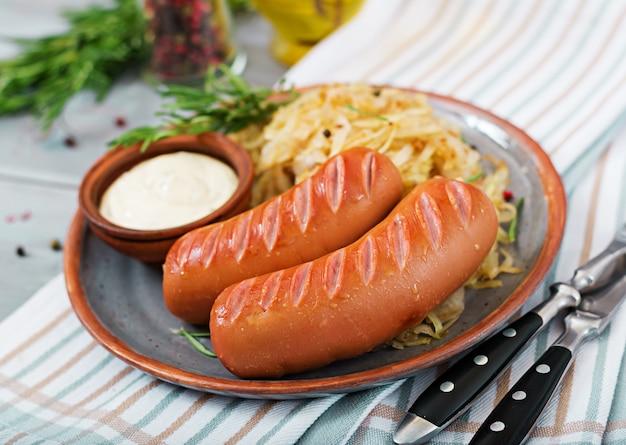 Prato de salsichas e chucrute na mesa de madeira. menu tradicional da oktoberfest