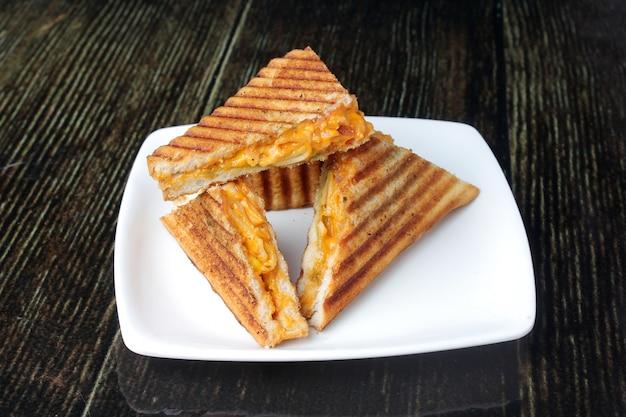 Prato de sanduíche grelhado na mesa de madeira