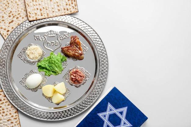 Prato de seder de páscoa com comida tradicional em fundo claro