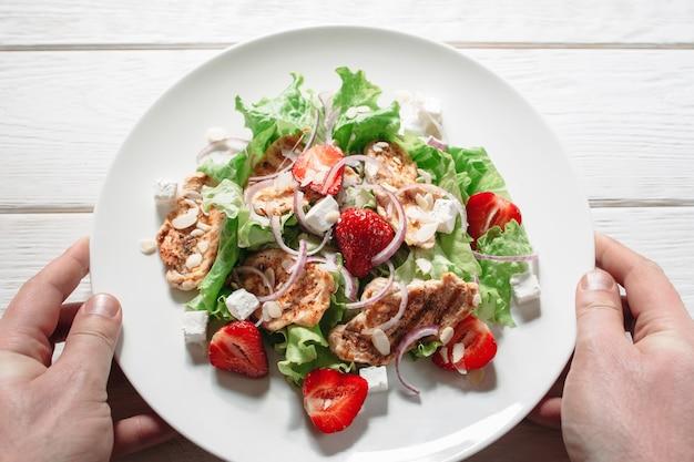 Prato de servir com bifes e salada fresca à mão masculina