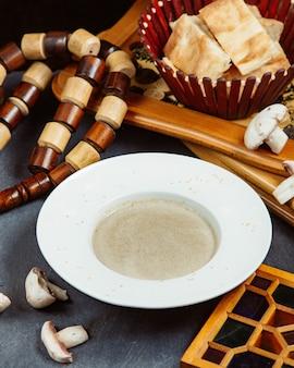 Prato de sopa de cogumelos servido com pão