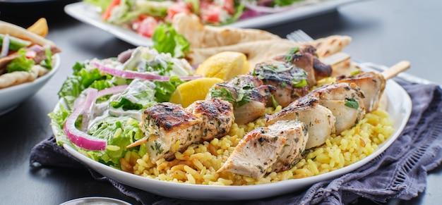 Prato de souvlaki de frango grego com pão sírio, salada e arroz