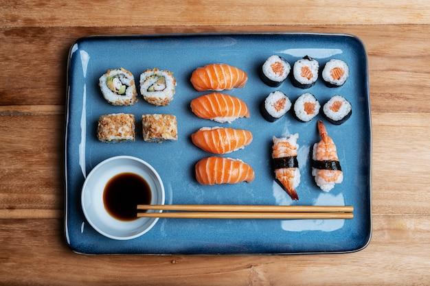 Prato de sushi com maki, uramaki, nigiri e california roll num prato azul, soja e pauzinhos. composição de alimentos gastronômicos asiáticos em fundo de madeira.