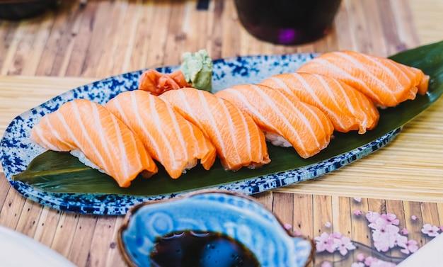 Prato de sushi composto por nigiri de salmão com molho de soja servido na varanda
